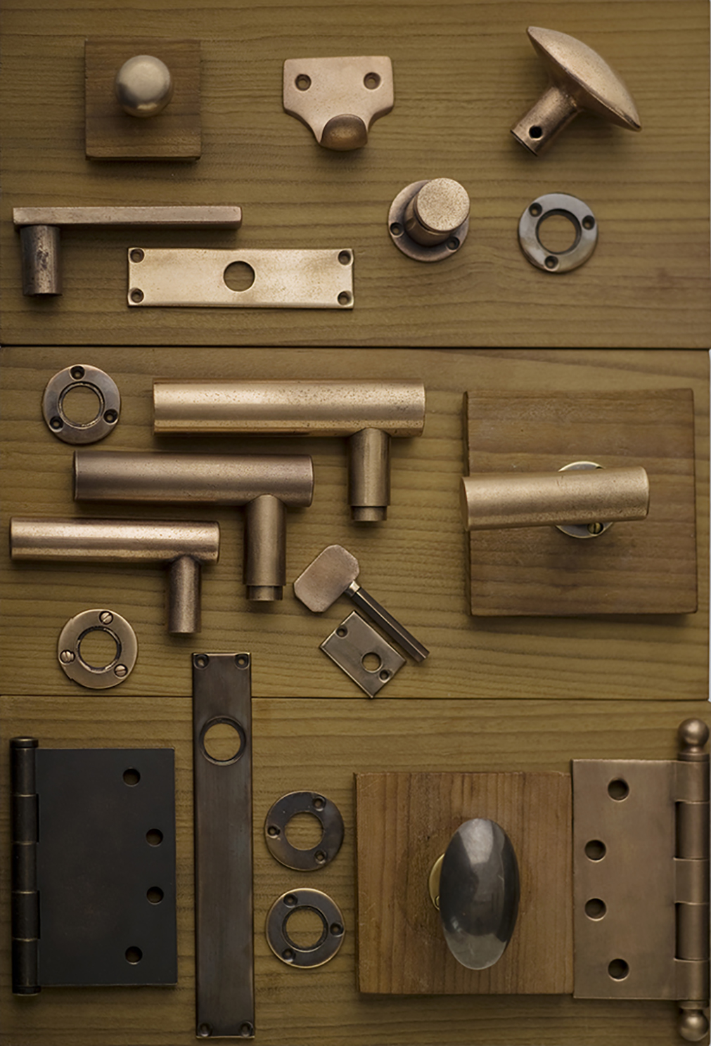 Collection of minimalist solid bronze hardware in a distressed custom finish.