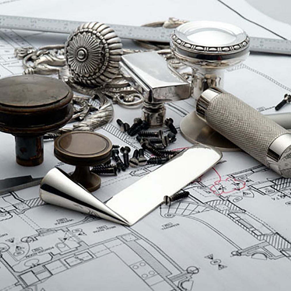 Collection of custom hardware placed on top of architectural drawings and floor plans.